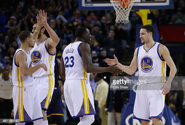 Klay Thompson of the Golden State Warriors celebrates with Andrew Bogut Draymond Green and Stephen Curry of the Golden State Warriors after he made a...