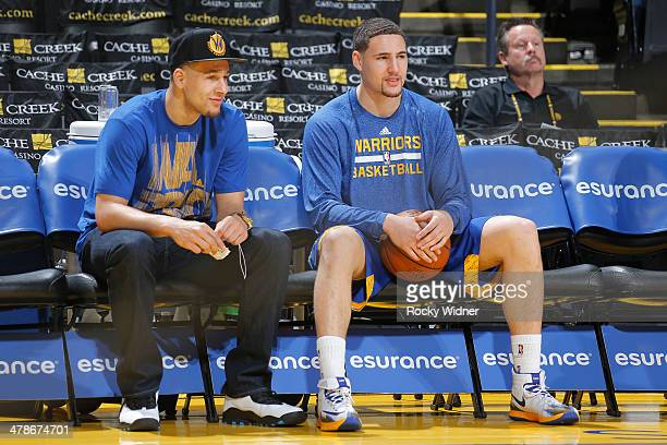 Klay Thompson of the Golden State Warriors chats with his younger brother Mychel Thompson before a game against the Phoenix Suns on March 9 2014 at...