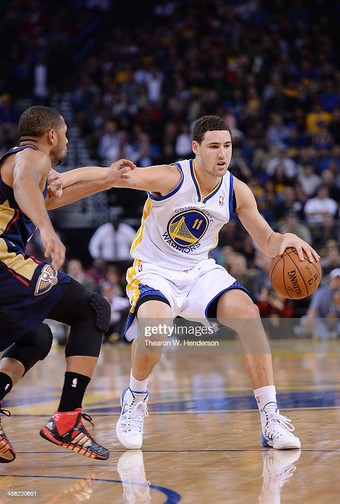 Klay Thompson #11 of the Golden State Warriors dribbles the ball, defended by Eric Gordon #10 of the New Orleans Pelicans at ORACLE Arena on December 17, 2013 in Oakland, California.