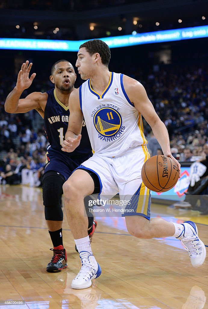 Klay Thompson #11 of the Golden State Warriors dribbles the ball past Eric Gordon #10 of the New Orleans Pelicans at ORACLE Arena on December 17, 2013 in Oakland, California.