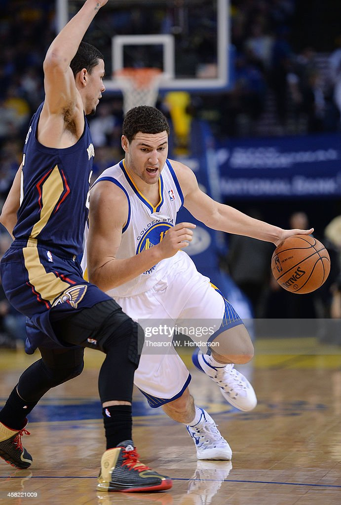 Klay Thompson #11 of the Golden State Warriors drives on Austin Rivers #25 of the New Orleans Pelicans at ORACLE Arena on December 17, 2013 in Oakland, California.