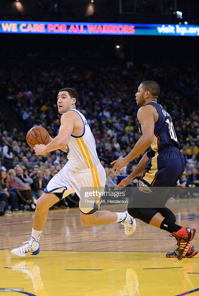 Klay Thompson #11 of the Golden State Warriors drives on Eric Gordon #10 of the New Orleans Pelicans at ORACLE Arena on December 17, 2013 in Oakland, California.