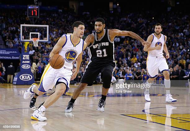 Klay Thompson of the Golden State Warriors drives on Tim Duncan of the San Antonio Spurs at ORACLE Arena on November 11 2014 in Oakland California...