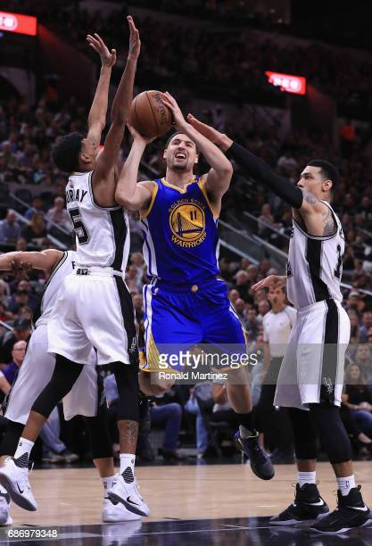 Klay Thompson of the Golden State Warriors drives to the basket against Dejounte Murray and Danny Green of the San Antonio Spurs in the first half...