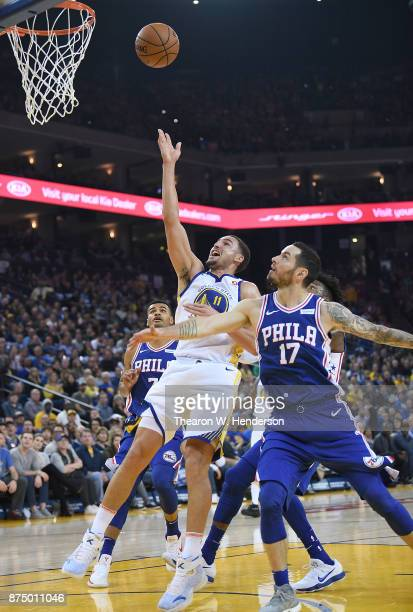Klay Thompson of the Golden State Warriors drives towards the basket on JJ Redick of the Philadelphia 76ers during an NBA basketball game at ORACLE...