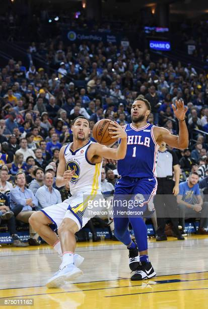 Klay Thompson of the Golden State Warriors drives towards the basket past Justin Anderson of the Philadelphia 76ers during an NBA basketball game at...
