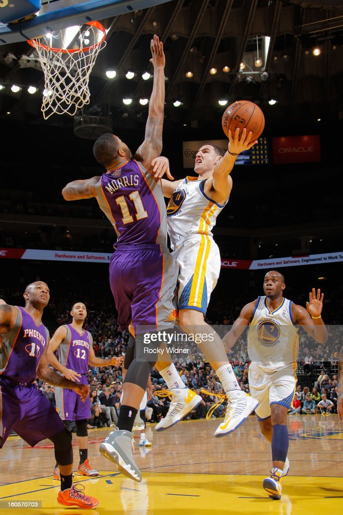 Klay Thompson #11 of the Golden State Warriors goes to the basket against Markieff Morris #11 of the Phoenix Suns on February 2, 2013 at Oracle Arena in Oakland, California.