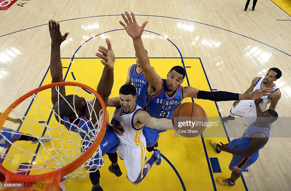 Klay Thompson #11 of the Golden State Warriors goes up for a shot against Serge Ibaka #9 and Andre Roberson #21 of the Oklahoma City Thunder in the first half of Game Seven of the Western Conference Finals during the 2016 NBA Playoffs at ORACLE Arena on May 30, 2016 in Oakland, California.