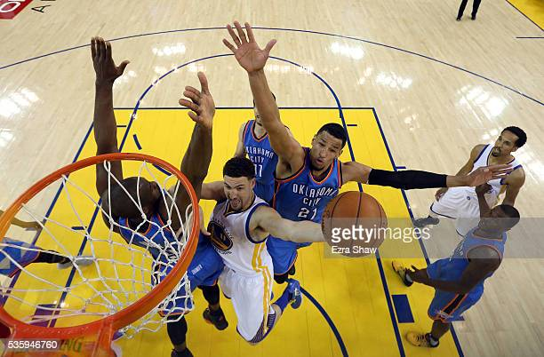 Klay Thompson of the Golden State Warriors goes up for a shot against Serge Ibaka and Andre Roberson of the Oklahoma City Thunder in the first half...