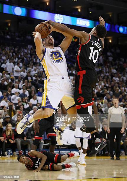 Klay Thompson of the Golden State Warriors goes up for a shot against DeMar DeRozan of the Toronto Raptors while Kyle Lowry of the Toronto Raptors...