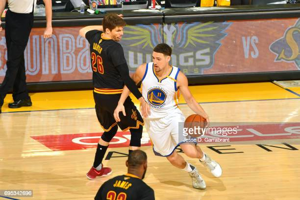 Klay Thompson of the Golden State Warriors handles the ball against Kyle Korver of the Cleveland Cavaliers in Game Five of the 2017 NBA Finals on...
