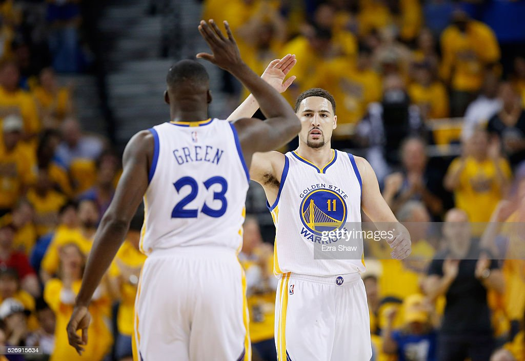 Klay Thompson #11 of the Golden State Warriors high-fives Draymond Green #23 during the first quarter against the Portland Trail Blazers during Game One of the Western Conference Semifinals for the 2016 NBA Playoffs at ORACLE Arena on May 01, 2016 in Oakland, California.