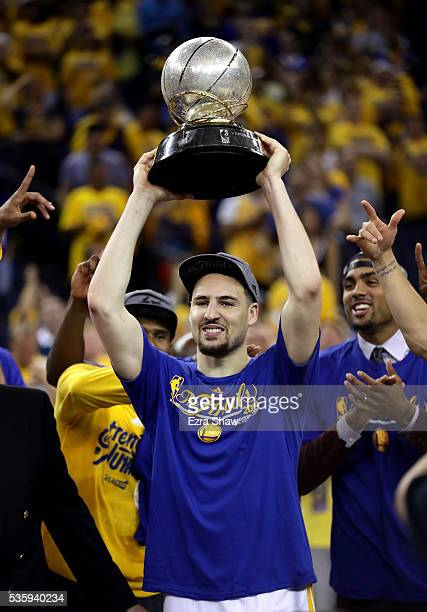 Klay Thompson of the Golden State Warriors holds up the Western Conference Trophy after they beat the Oklahoma City Thunder in Game Seven of the...