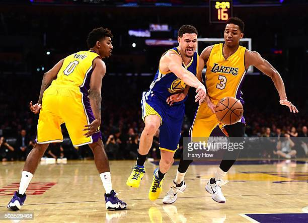 Klay Thompson of the Golden State Warriors is fouled ashe dribble between Anthony Brown and Nick Young of the Los Angeles Lakers during the first...