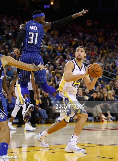 Klay Thompson of the Golden State Warriors is guarded by Terrence Ross of the Orlando Magic at ORACLE Arena on November 13 2017 in Oakland California...