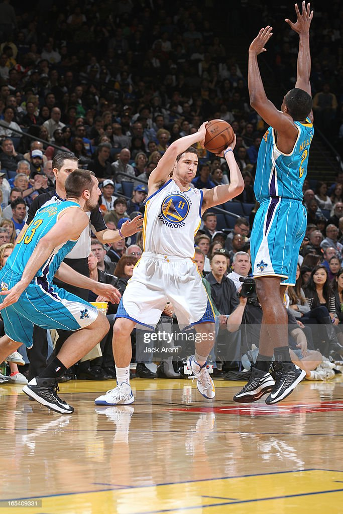Klay Thompson #11 of the Golden State Warriors looks to pass the ball against Ryan Anderson #33 and Darius Miller #2 of the New Orleans Hornets on April 3, 2013 at Oracle Arena in Oakland, California.