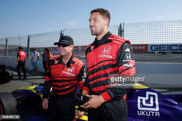 Klay Thompson of the Golden State Warriors NBA team meets driver Davey Hamilton after a ride in a twoseat IndyCar on day 3 of the GoPro Grand Prix of...