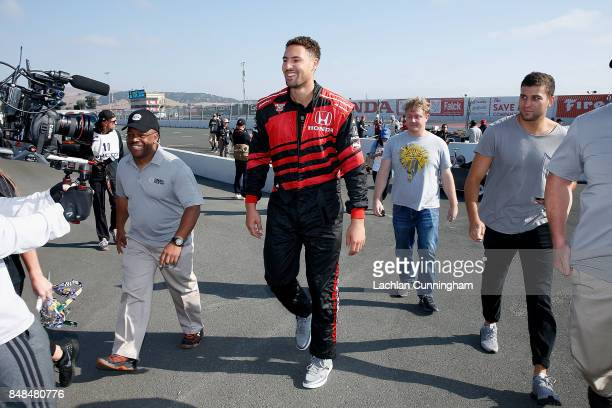 Klay Thompson of the Golden State Warriors NBA team walks from the track after a ride in a twoseat IndyCar with driver Davey Hamilton on day 3 of the...
