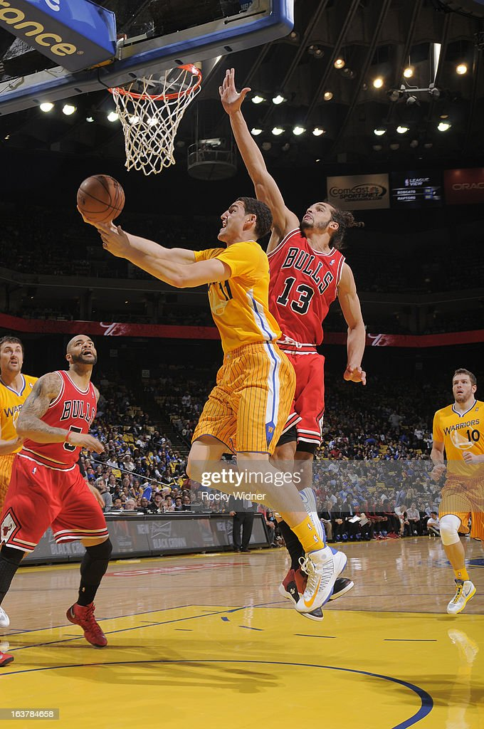 Klay Thompson #11 of the Golden State Warriors shoots a layup against Joakim Noah #13 of the Chicago Bulls on March 15, 2013 at Oracle Arena in Oakland, California.