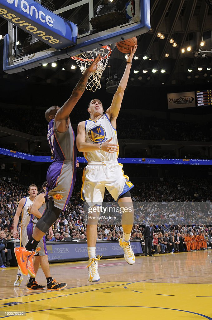 Klay Thompson #11 of the Golden State Warriors shoots a layup against P.J. Tucker #17 of the Phoenix Suns on February 2, 2013 at Oracle Arena in Oakland, California.