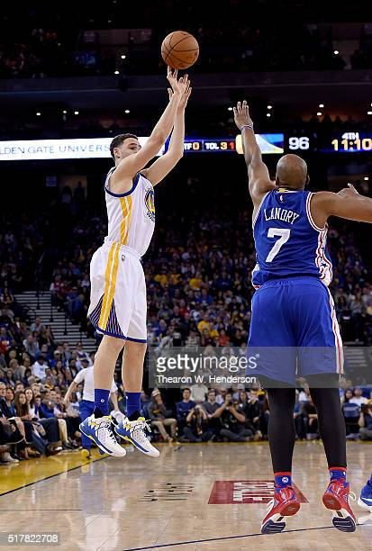 Klay Thompson of the Golden State Warriors shoots a threepoint shot over Carl Landry of the Philadelphia 76ers during an NBA Basketball game at...
