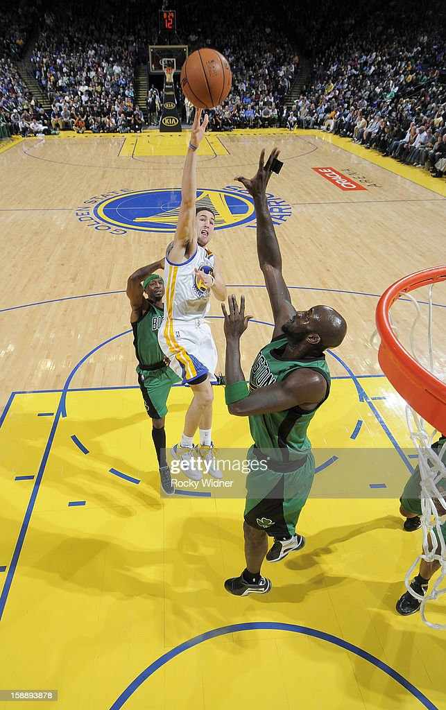 Klay Thompson #11 of the Golden State Warriors shoots against Kevin Garnett #5 of the Boston Celtics on December 29, 2012 at Oracle Arena in Oakland, California.