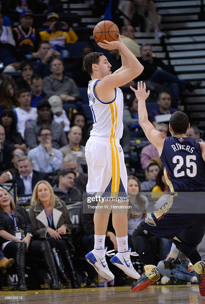 Klay Thompson #11 of the Golden State Warriors shoots over Austin Rivers #25 of the New Orleans Pelicans at ORACLE Arena on December 17, 2013 in Oakland, California.