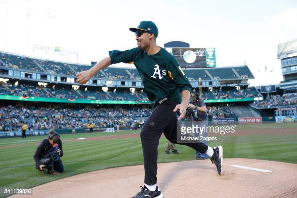 Klay Thompson of the Golden State Warrios throws out the ceremonial first pitch prior to the game between the Oakland Athletics and the San Francisco...