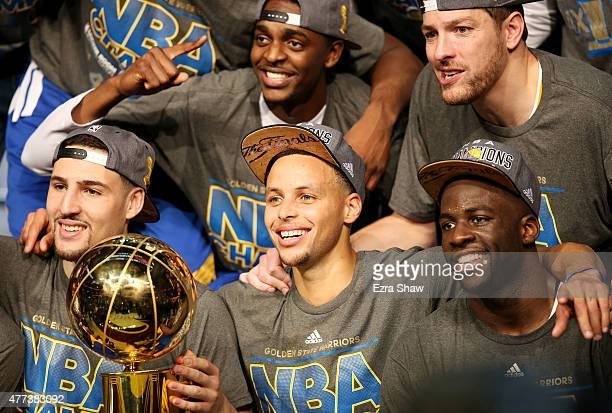 Klay Thompson Stephen Curry and Draymond Green of the Golden State Warriors celebrate with the Larry O'Brien NBA Championship Trophy after defeating...
