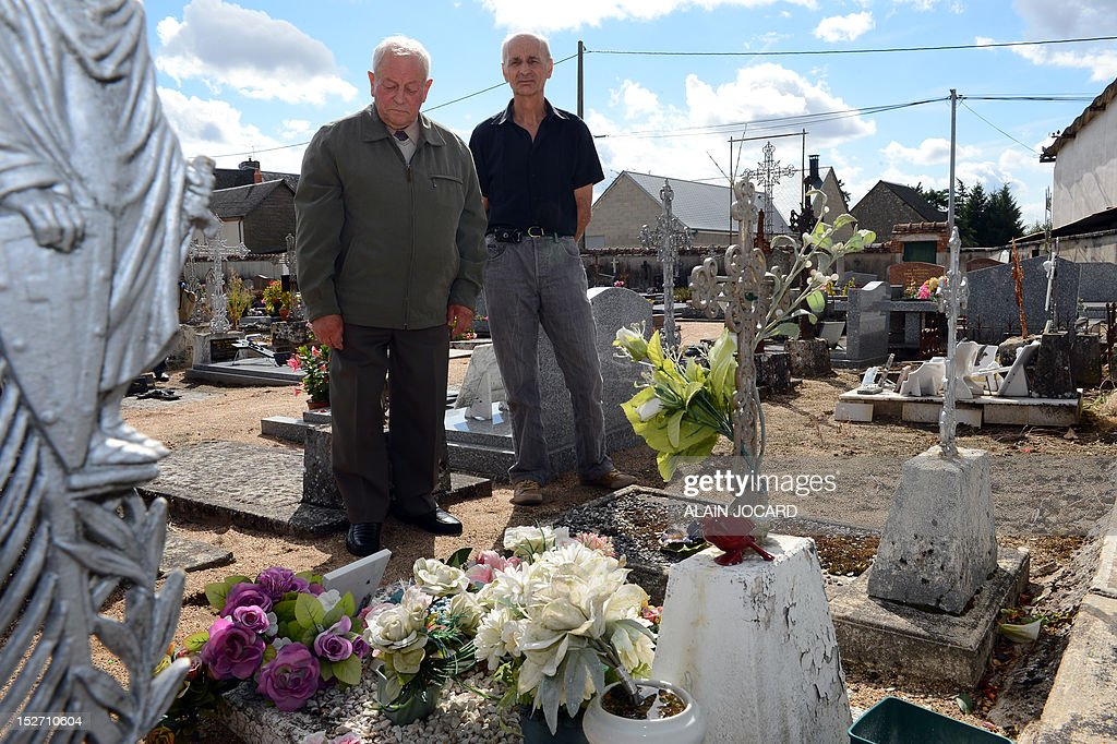 Kleber Cousin (L) and Raphael Pilleboue, respectively former and actual mayor of the western French city of Suevres stand in front of the grave of an unidentified three or four-year-old victim of a crime on September 24, 2012 at the Suevres cemetary. Blois' prosecutor, Dominique Puechmaille decided to reopen the case of the victim found on August, 11, 1987 on the motor highway A10, near Blois.