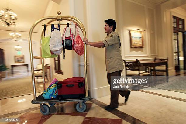 Kleber Vera a bellman at the RitzCarlton Key Biscayne hotel wheels a guests luggage to their room on July 27 2010 in Key Biscayne Florida According...