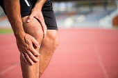 knee Injuries. young sport man with strong athletic legs holding knee with his hands in pain after suffering muscle injury during a running workout training on Running Track. Healthcare and sport conc