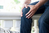 A male person sitting on a balcony with sudden knee-pain.