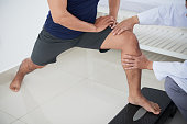 Cropped image of physiotherapist giving knee theraphy to young man