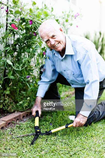Kneeling 90-year-old man happily clipping his garden lawn
