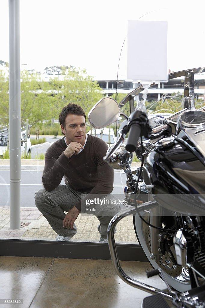 kneeling man admiring motorcylce through window : Stock Photo