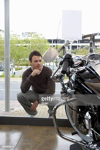 kneeling man admiring motorcylce through window