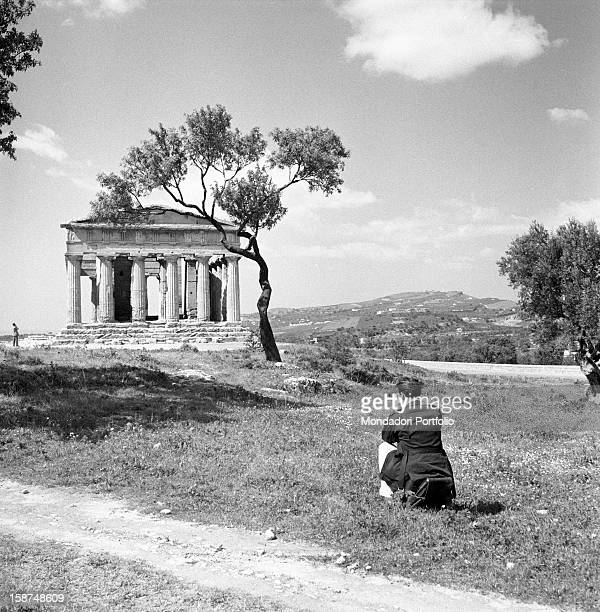 A kneeling man taking a picture of the Greek Temple of Concordia Agrigento 1955