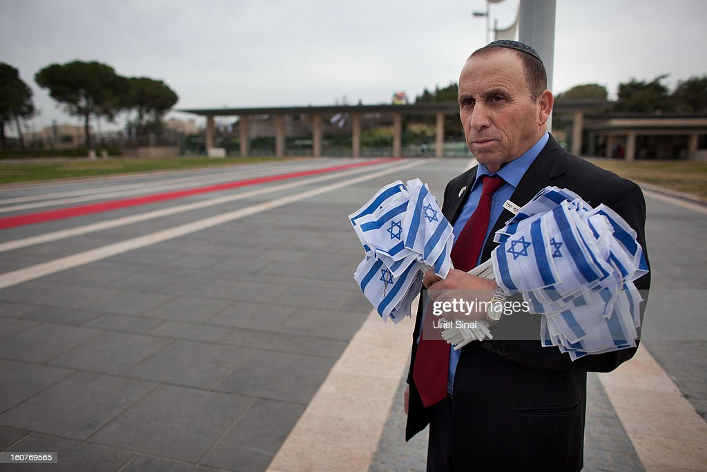 A Knesset worker holds Israeli flags ahead of a cermony marking the opening of the 19th Knesset (Israeli parliament) on February 5, 2013 in Jerusalem, Israel. The 120 members of the Knesset included a record 48 new law makers.