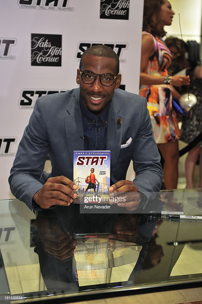 Knicks basketball player Amar'e Stoudemire poses with new book for Fashion's Night Out at Saks Fifth Avenue on September 6, 2012 in New York City.