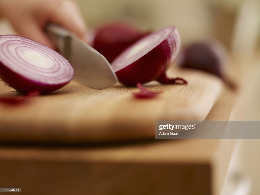 Knife chopping red onion on cutting board : Stock Photo