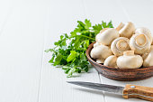 A knife next to a bowl of mushrooms and a bunch of parsley on a white table. Vegetarian cuisine. Natural plant food.
