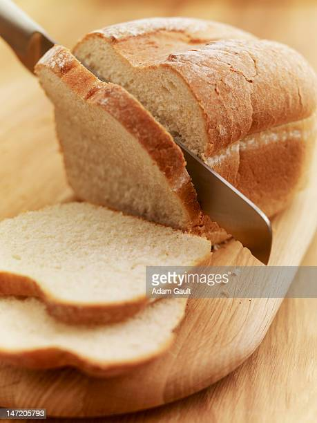 Knife slicing loaf of bread