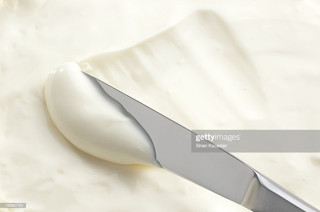 A knife swiping into some cream cheese