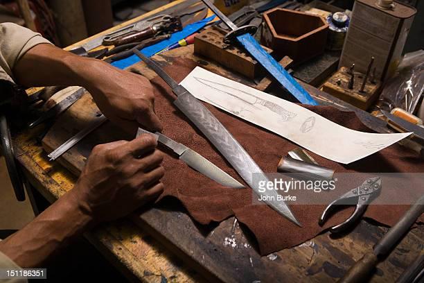 knifemaker polishing a Damascus steel blade