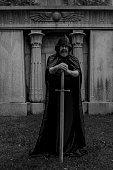 Man with a beard wearing a black hooded cape. He is a knight holding a large sword on the ground. Grave crypt in the background. Black and white.