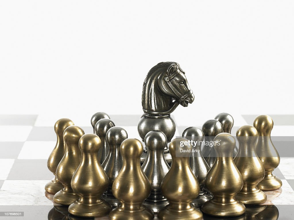 Knight surrounded by pawn chess pieces : Stock Photo