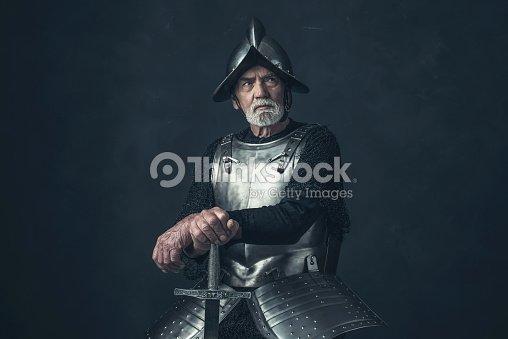 knight with beard in armor leaning on sword ストックフォト thinkstock