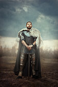 The courageous knight dressed in chain armor standing in a field leaning on his sword.