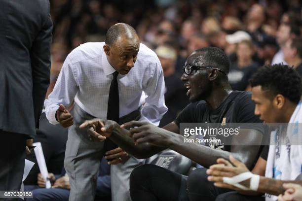Knights head coach Johnny Dawkins talks with UCF Knights center Tacko Fall during the 2017 NIT Championship quarterfinal game between the Illinois...